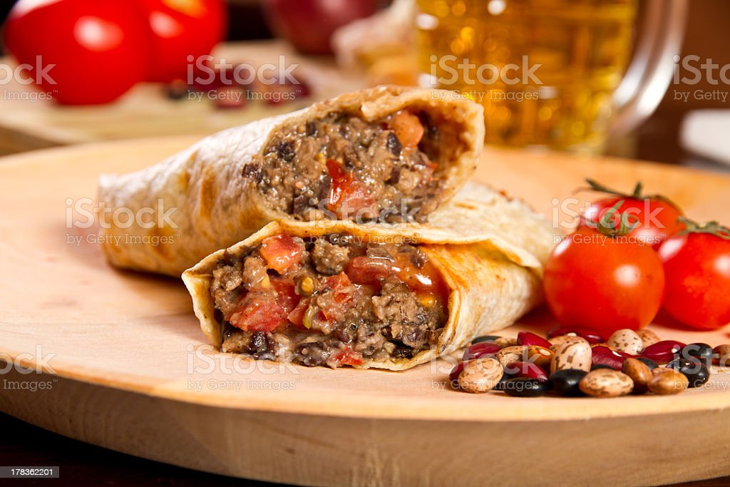 Bean and tomato tortilla sliced in half on wooden board stock photo
