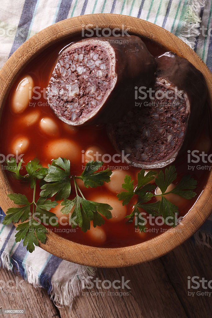 Bean soup with sausage morcilla closeup. vertical top view stock photo