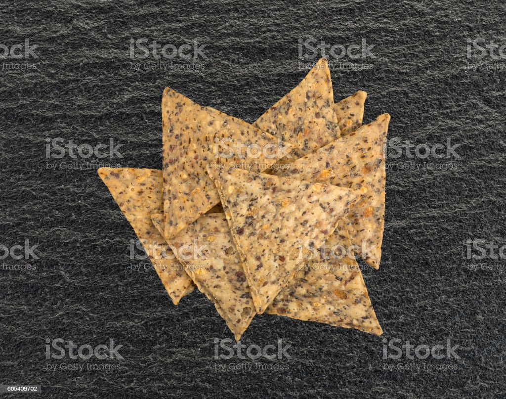 Beans and rice chips on a black cutting board stock photo