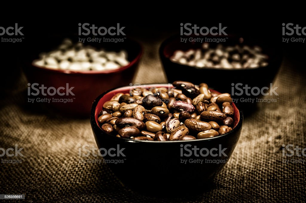 Beans in three bowls on sacking stock photo
