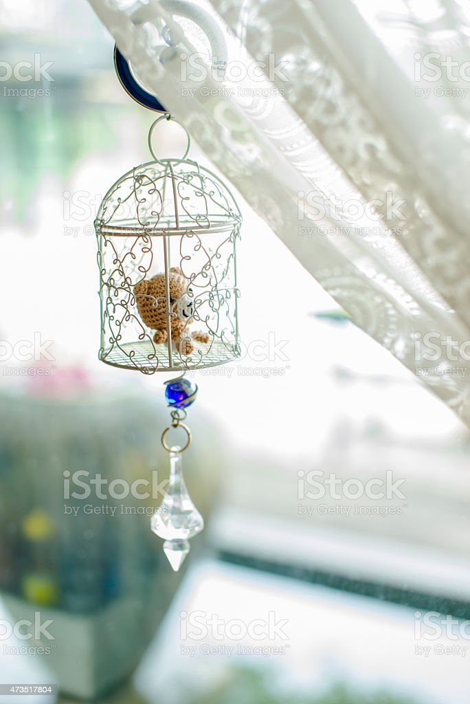 bear doll in cage hanging on window shades royalty-free stock photo