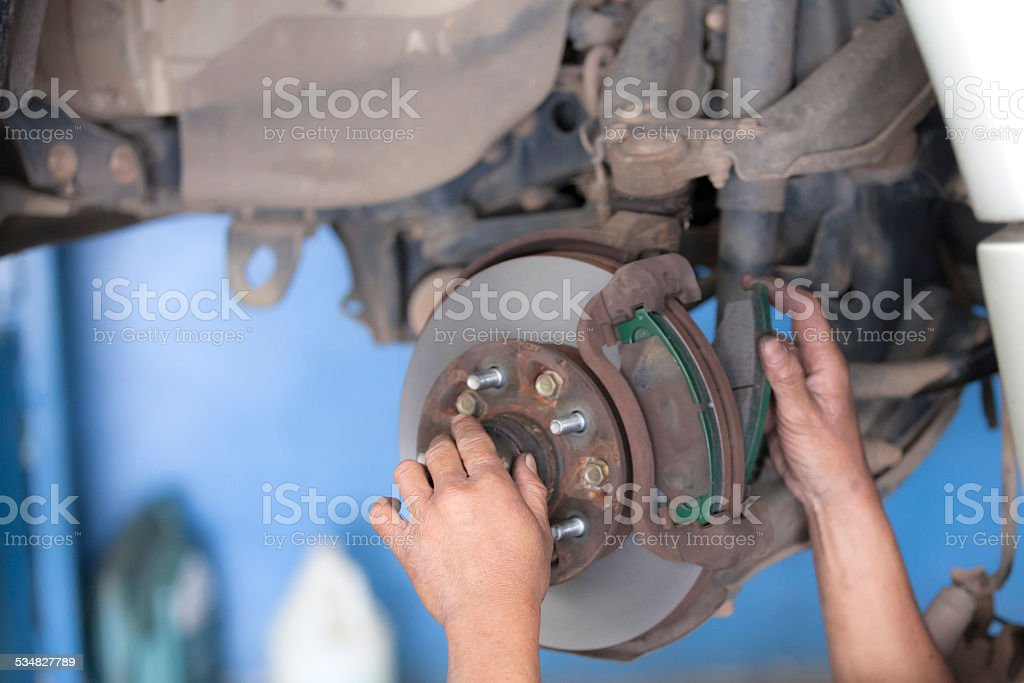 bear hands fixing car wheel hub, disc brake stock photo