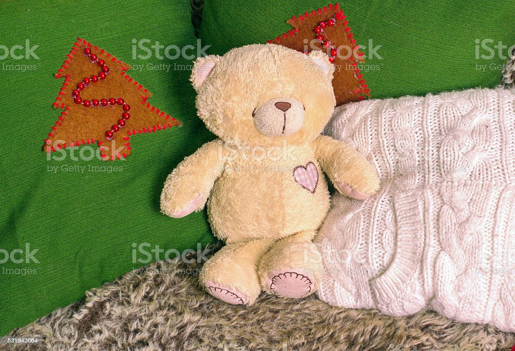 Bear toy on a sofa decorated with soft pillows stock photo