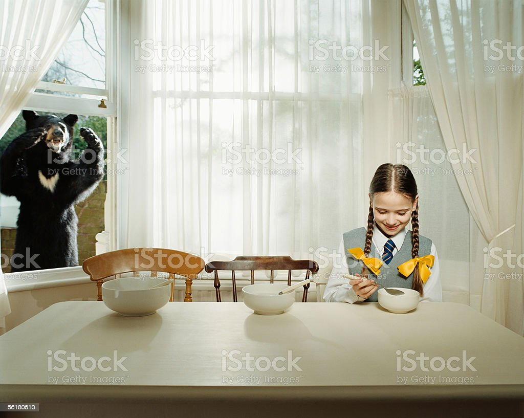 Bear watching girl eating stock photo