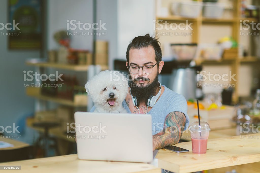 Beard Man Sitting In Cafe With His Dog stock photo