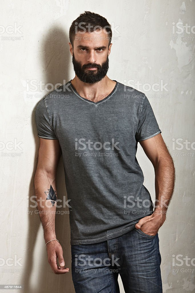 Bearded brutal man wearing grey t-shirt stock photo