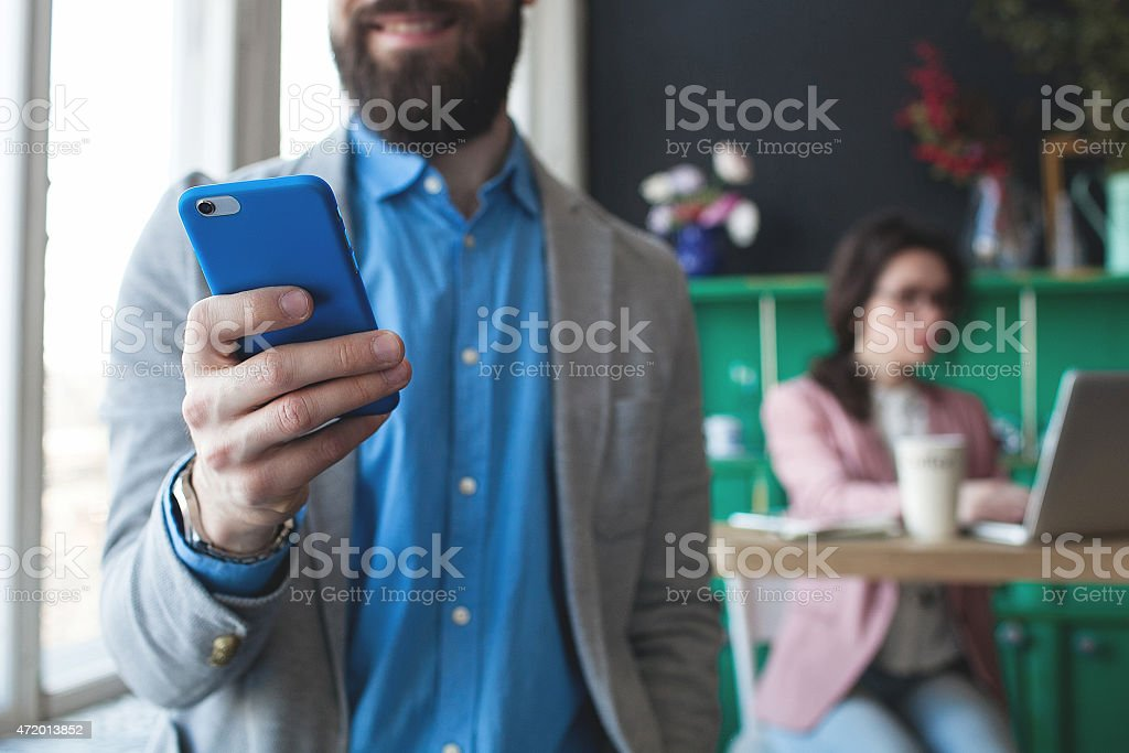 A bearded business man in glass looking at his phone stock photo
