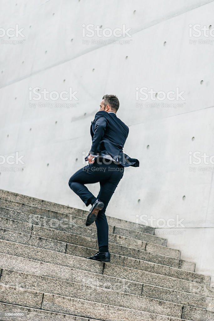 bearded business man running up outdoor stairway stock photo