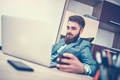 Bearded Businessman Drinking Coffee and Using Computer in his Office