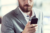 Bearded businessman using smart phone