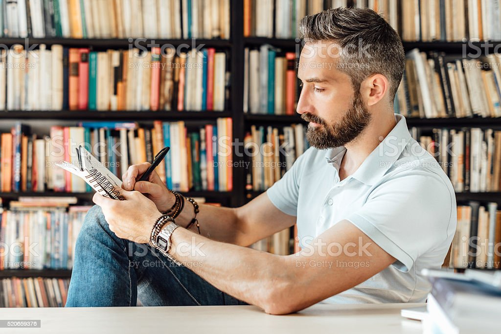 bearded creative man drawing in sketchbook stock photo