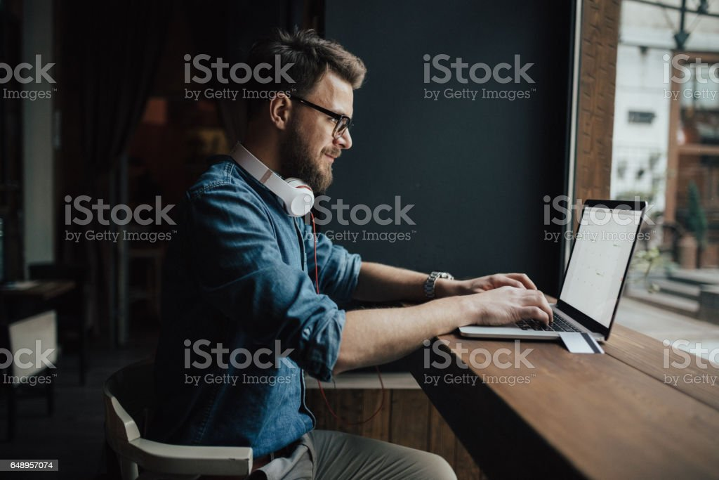 Bearded graphic designer checking schedule on laptop stock photo