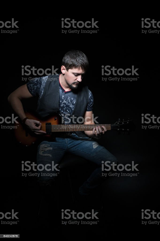 Bearded guitarist with an electric guitar stock photo