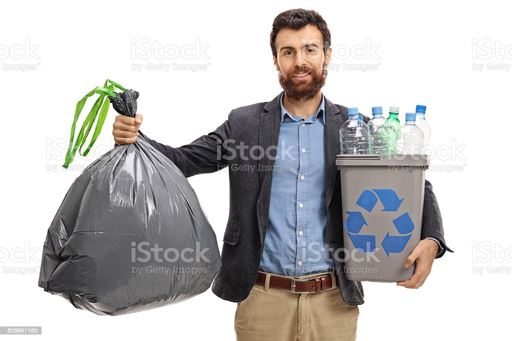 Bearded guy holding a garbage bag and a recycling bin stock photo