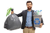 Bearded guy holding a garbage bag and a recycling bin