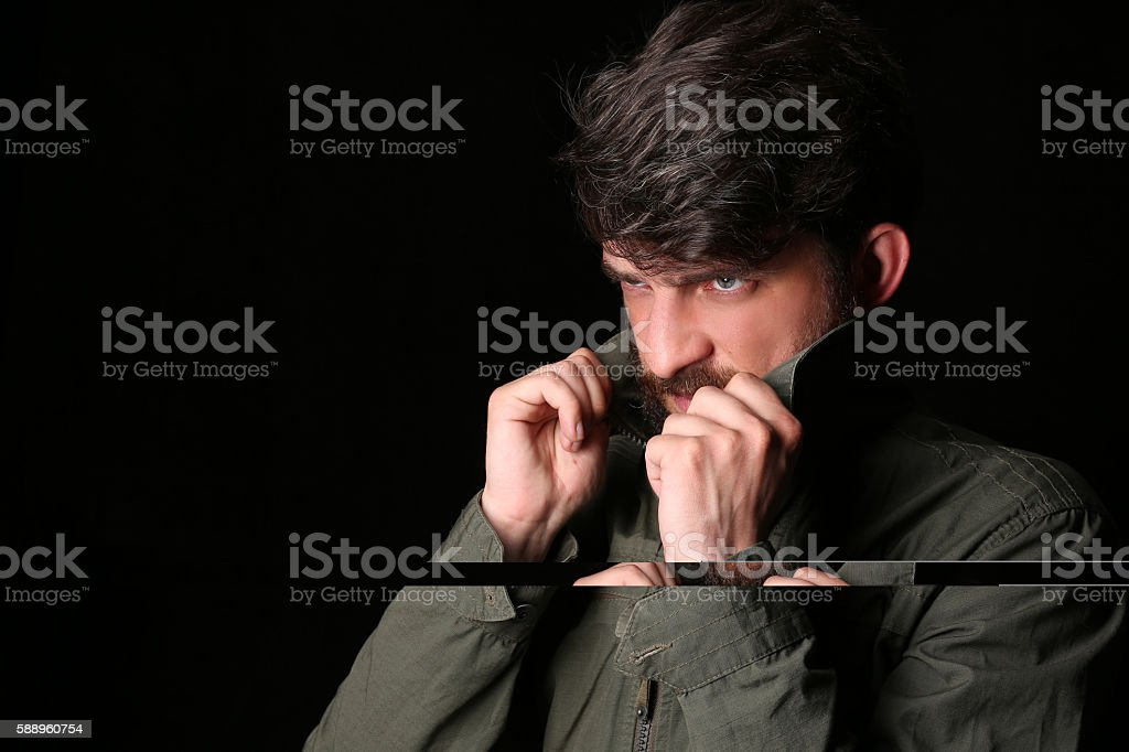 Bearded guy holding his collar. Close.up. Black stock photo