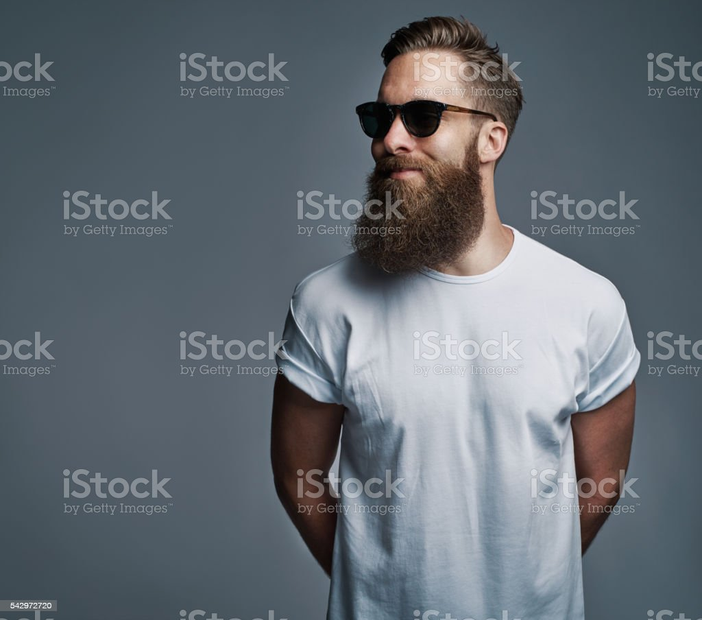 Bearded handsome man with sunglasses looking over stock photo