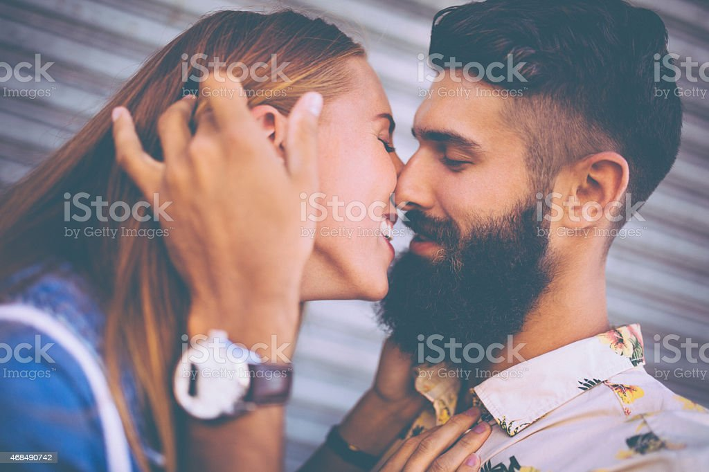 Bearded hipster guy and girl about to kiss happily stock photo