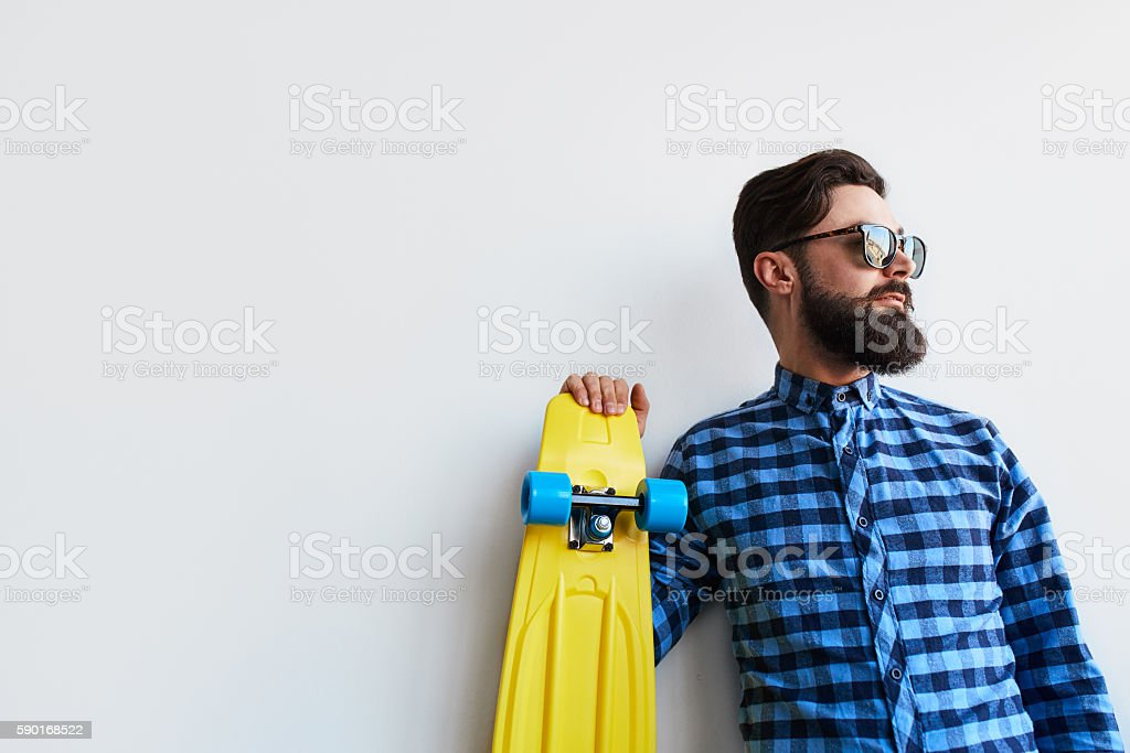bearded hipster in checkered shirt holding yellow skateboard stock photo