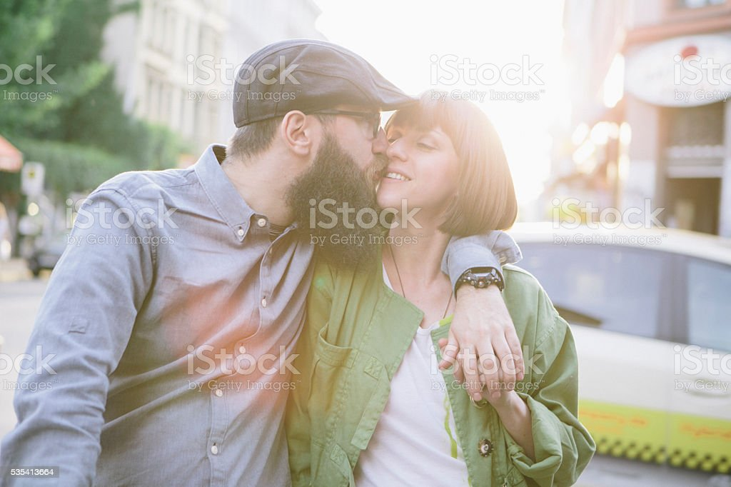 bearded hipster kiss his girlfriend on urban background stock photo