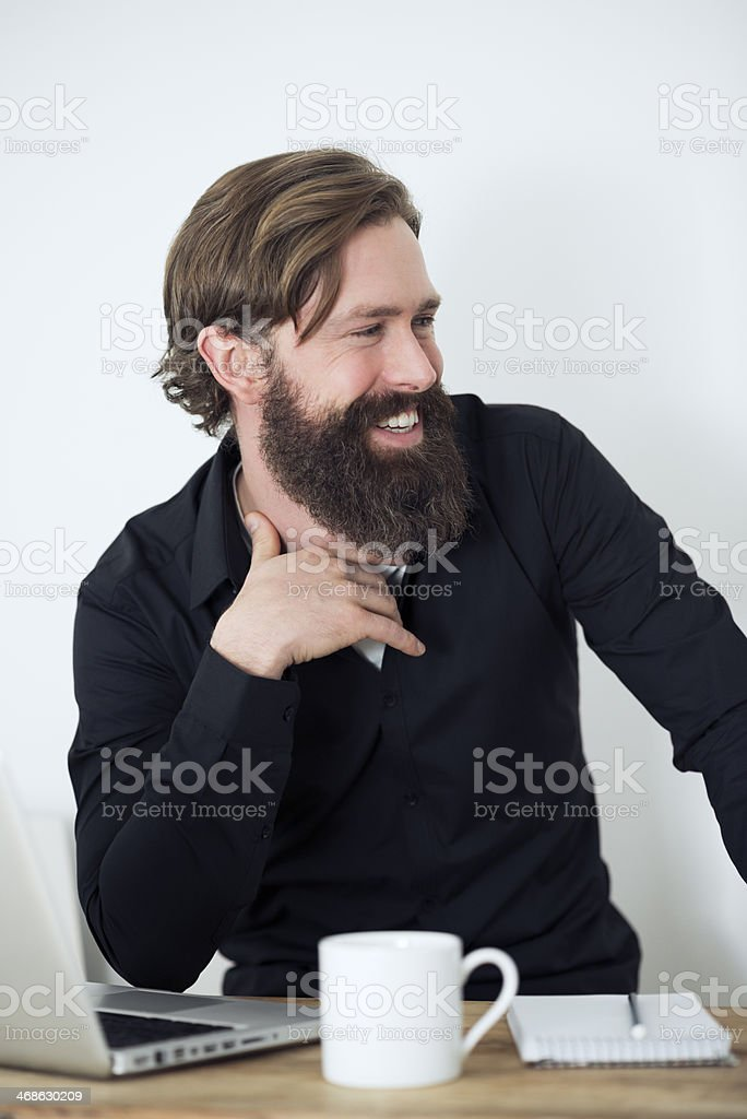 bearded laughing Man working at desk royalty-free stock photo