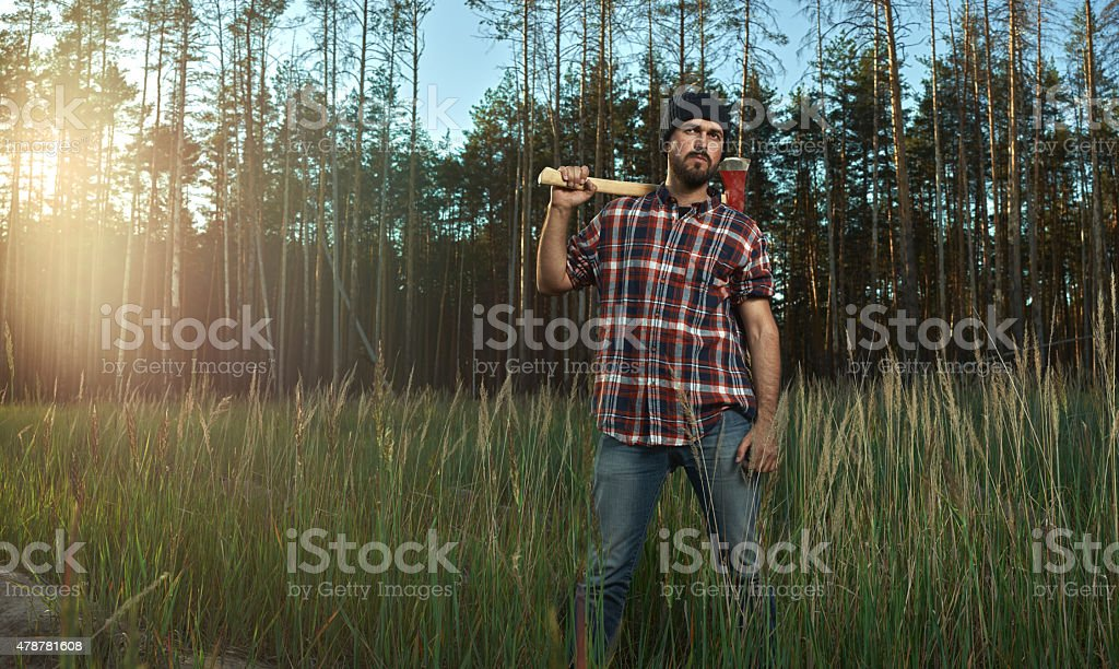 Bearded Lumberjack in Hat holding a big Axe on Shoulder stock photo