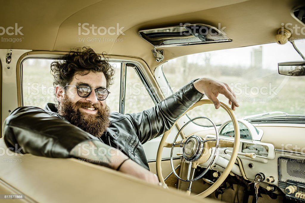 Bearded man behind the wheel of a retro car stock photo