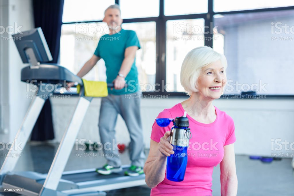 Bearded man exercising on treadmill while smiling woman drinking water in fitness class stock photo
