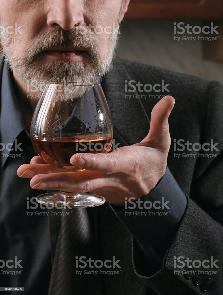 Bearded man holding a cognac glass between his fingers stock photo