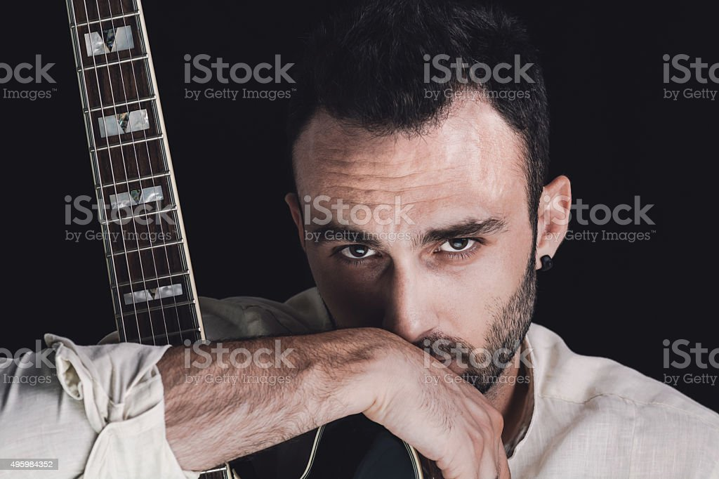 Bearded man holding his guitar stock photo