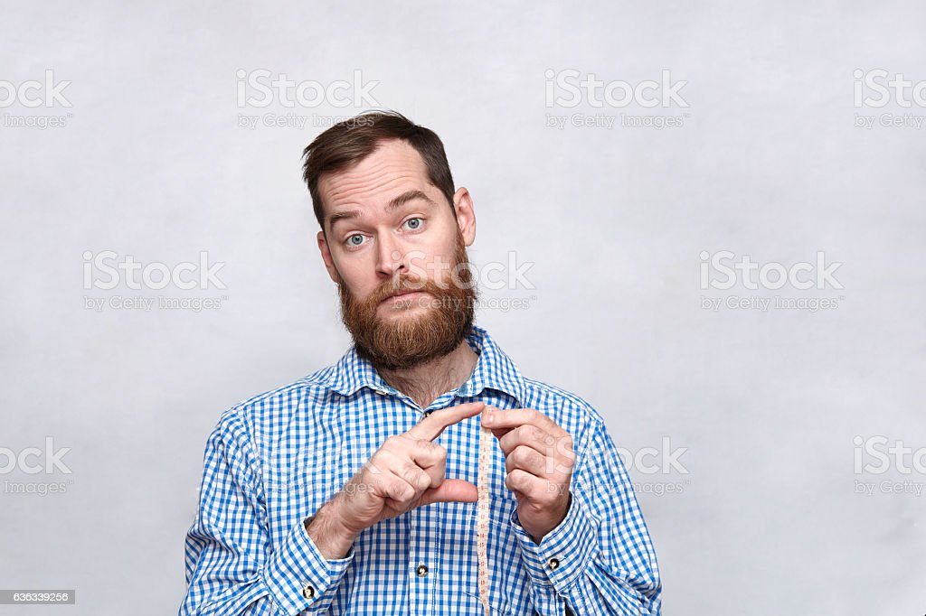Bearded man holding measuring tape and gesturing small size stock photo