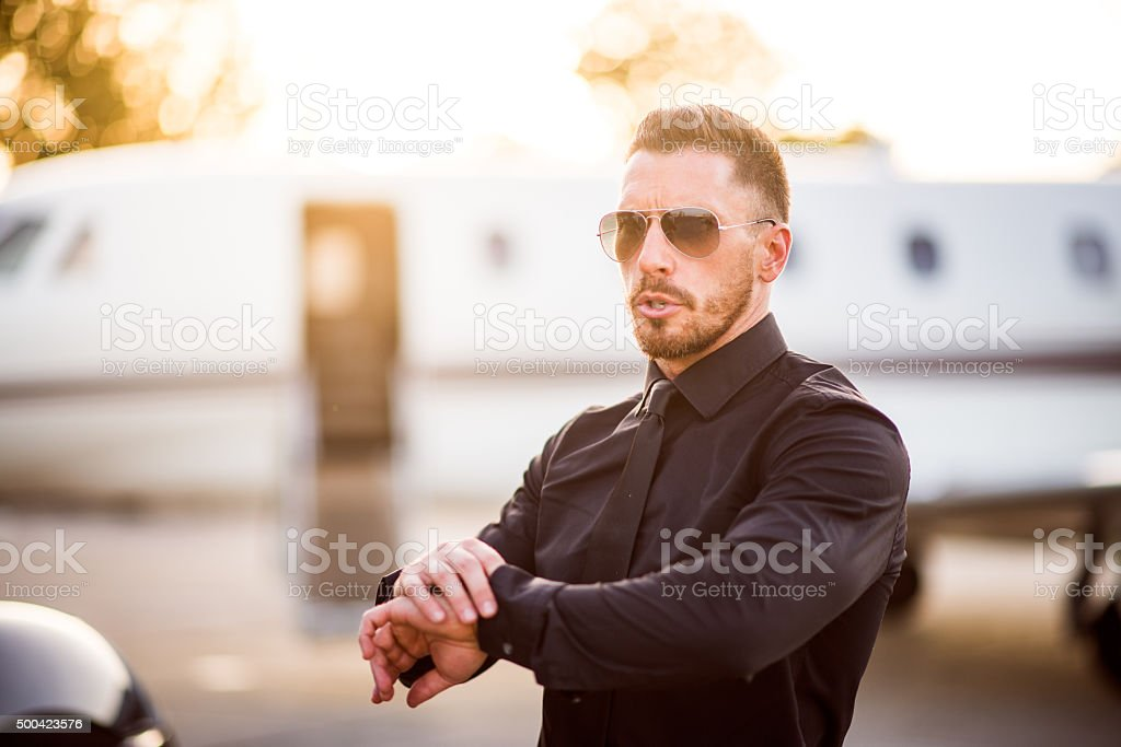 Bearded man in black suit holding his wrist stock photo