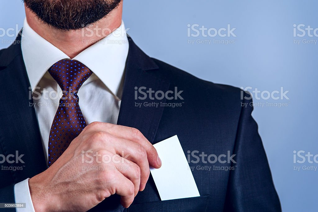 Bearded man in dark suit removes card to pocket stock photo