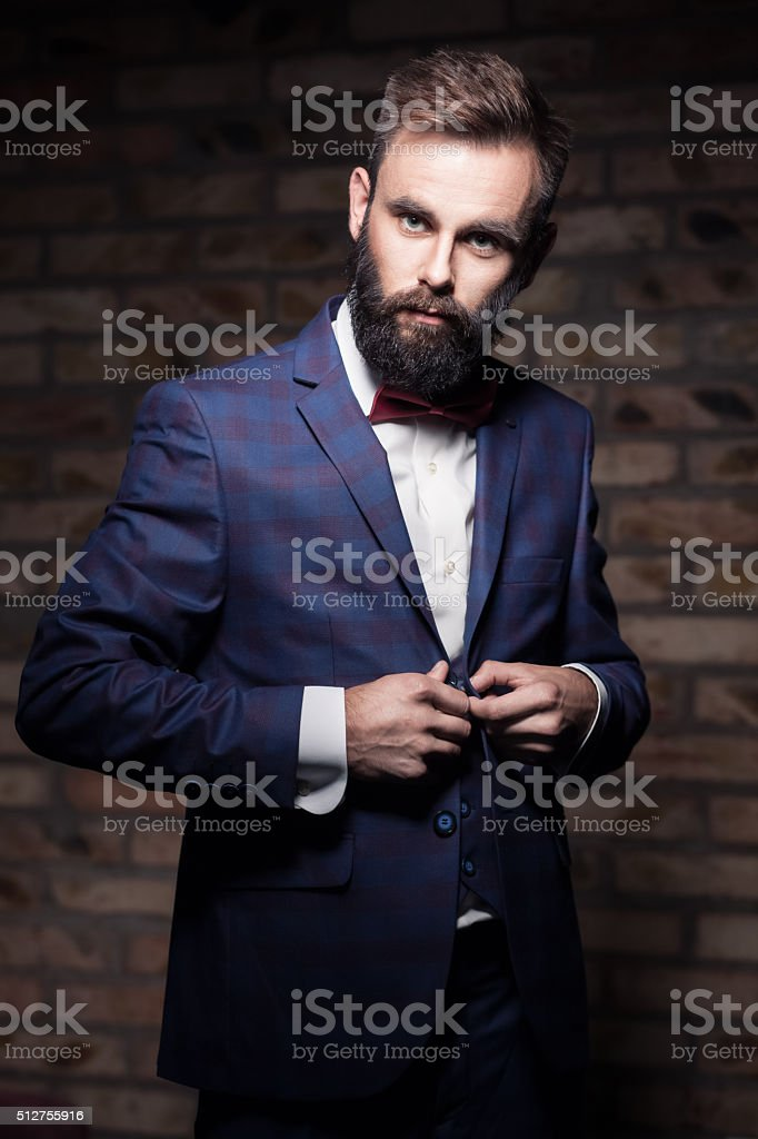 bearded man in suit staying by brick wall and buttoning stock photo