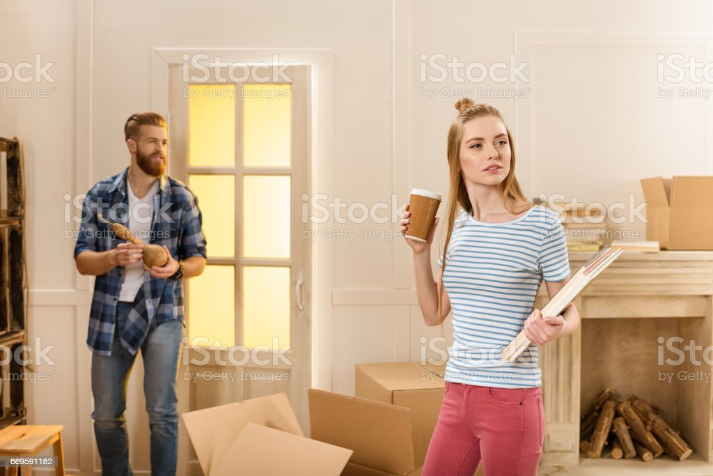 Bearded man looking at pensive woman with disposable cup and magazines in new house stock photo