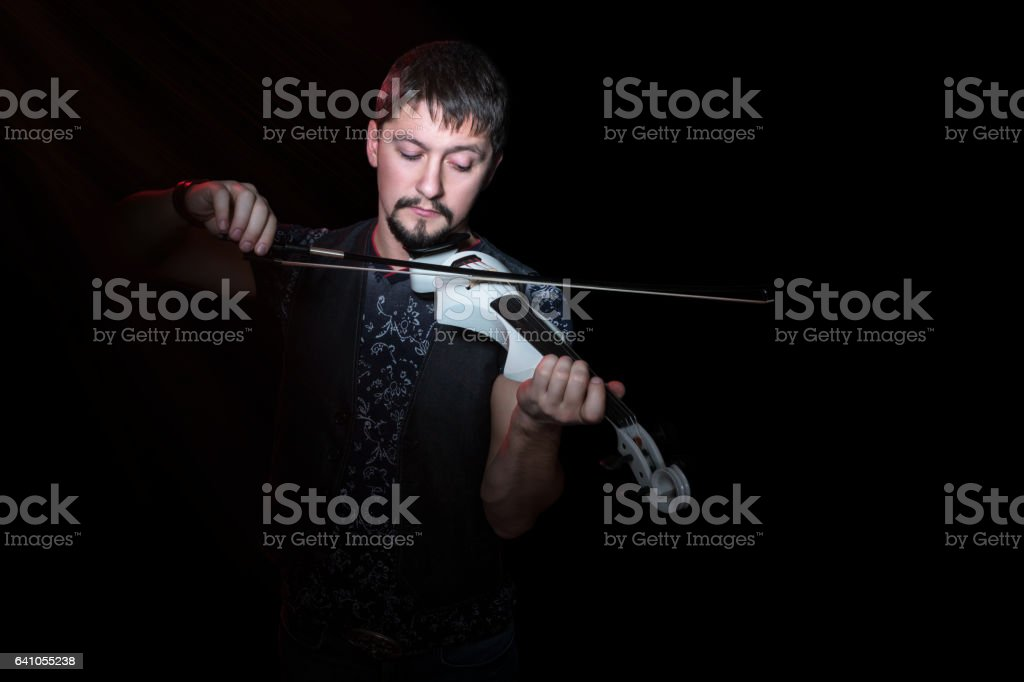 Bearded man playing on electroviolin stock photo