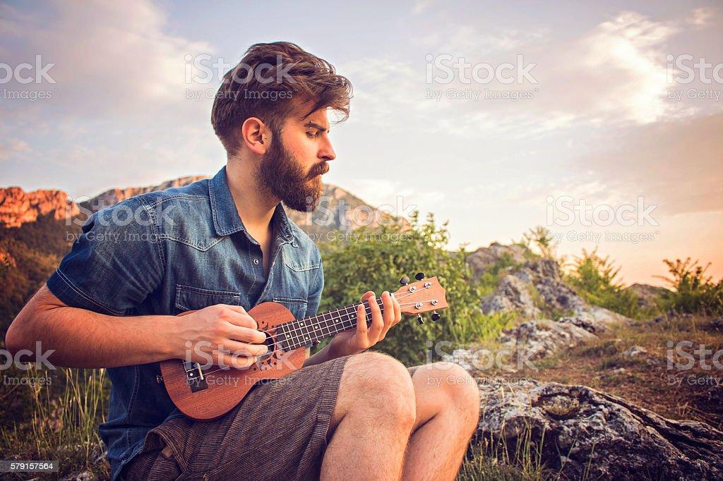 Bearded man playing ukulele on top of hill stock photo