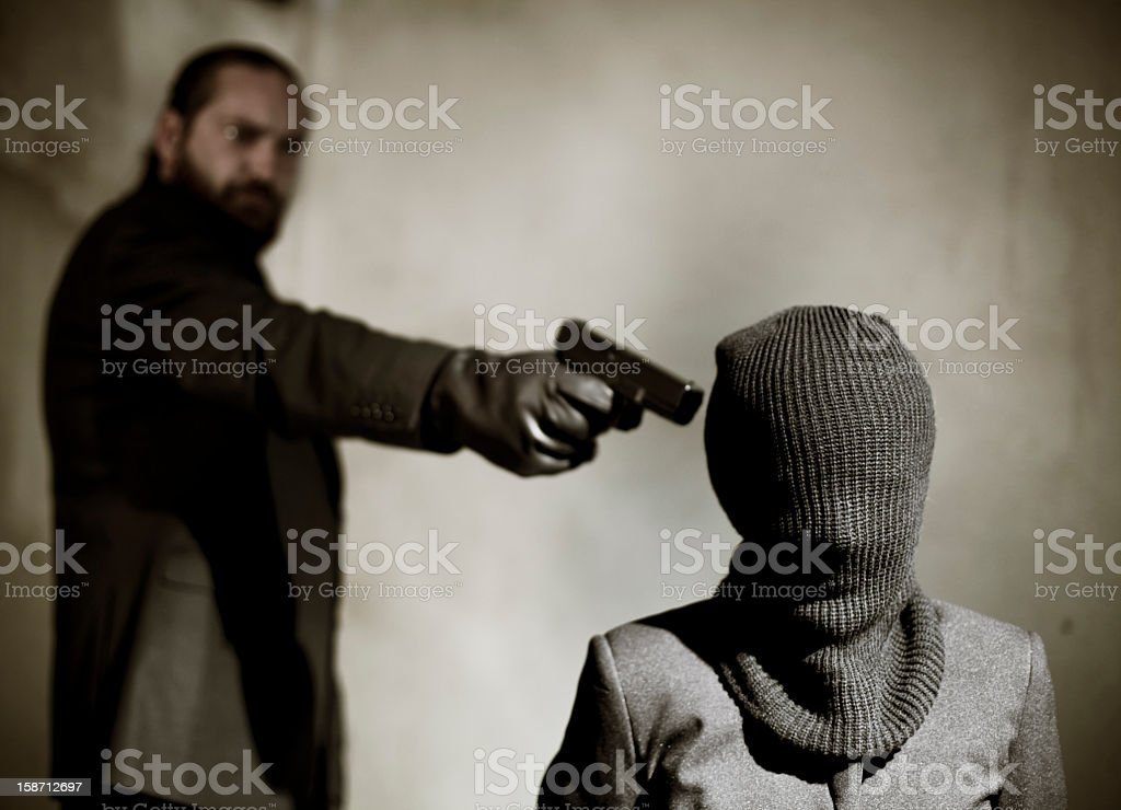 Bearded man pointing a gun at a man's temple to execute him stock photo