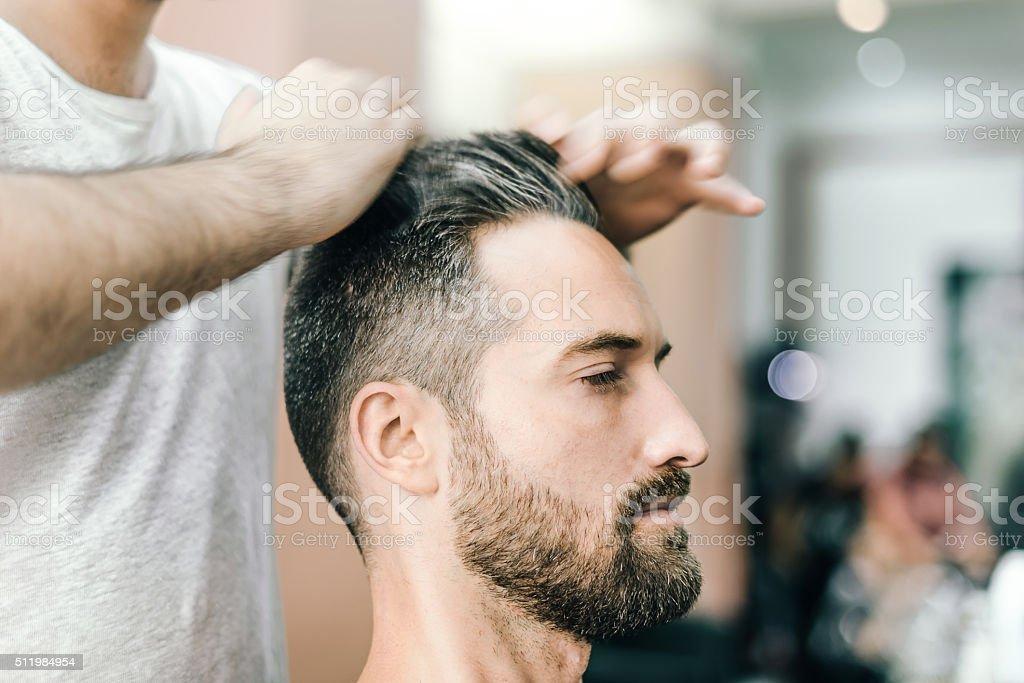 bearded man receiving haircut in the barbershop stock photo