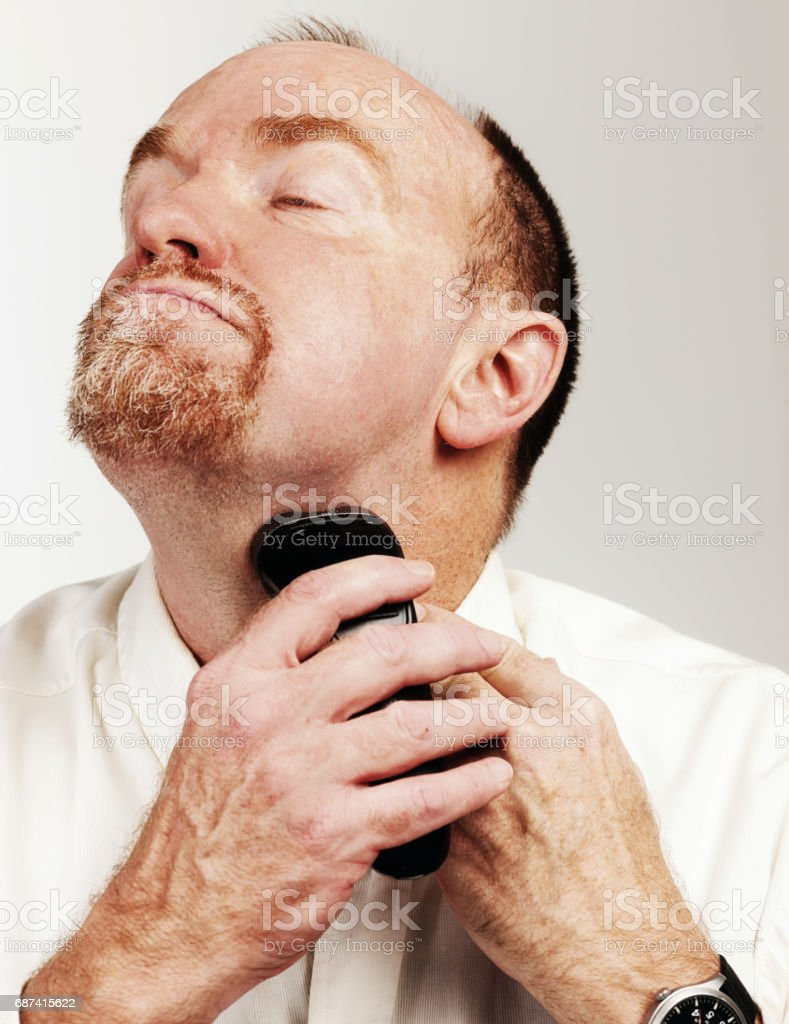Bearded man shaving with electric razor concentrates, neck stretched stock photo
