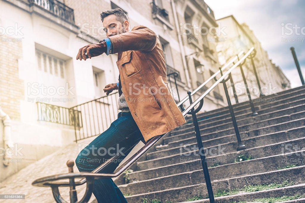bearded man sliding down the iron balustrade of monmartre stairs stock photo