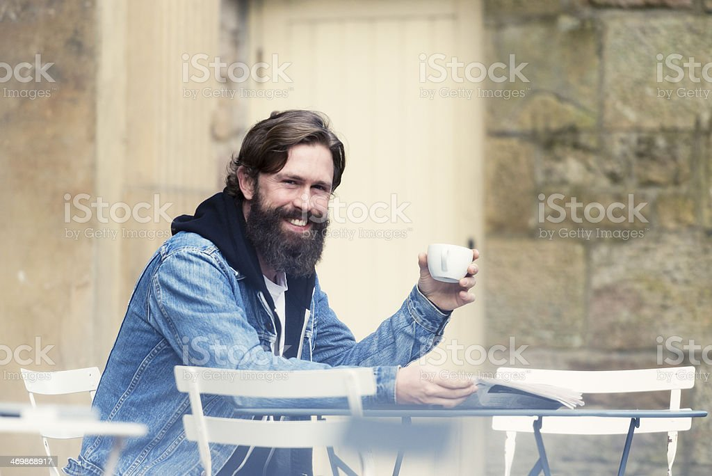 Bearded Man smiling while drinking coffee. royalty-free stock photo