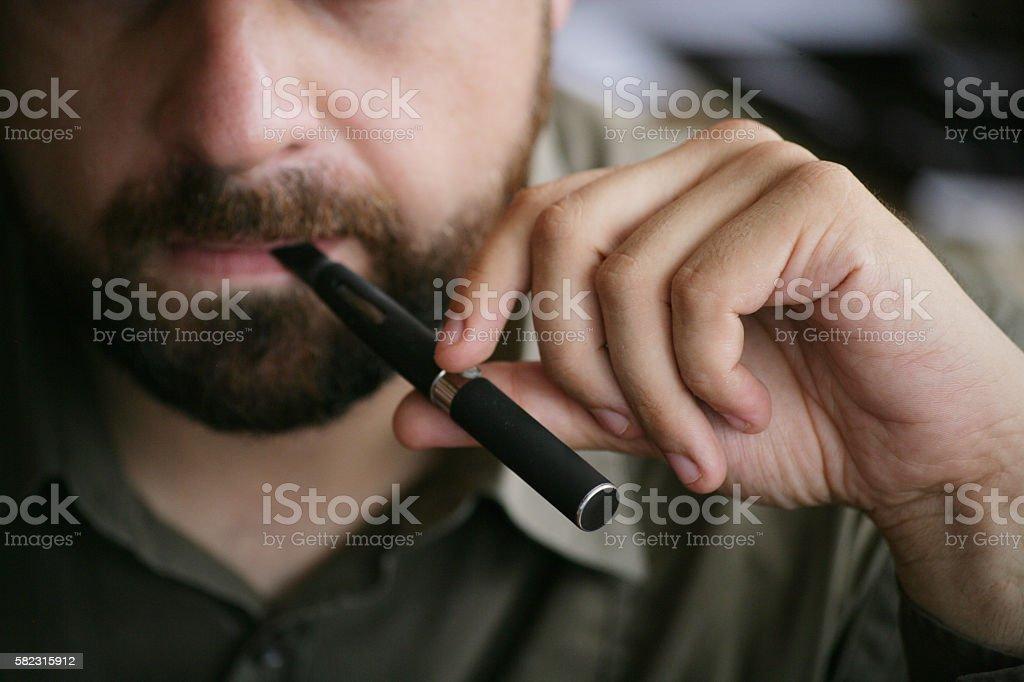 Bearded Man smoking e-cigarette stock photo