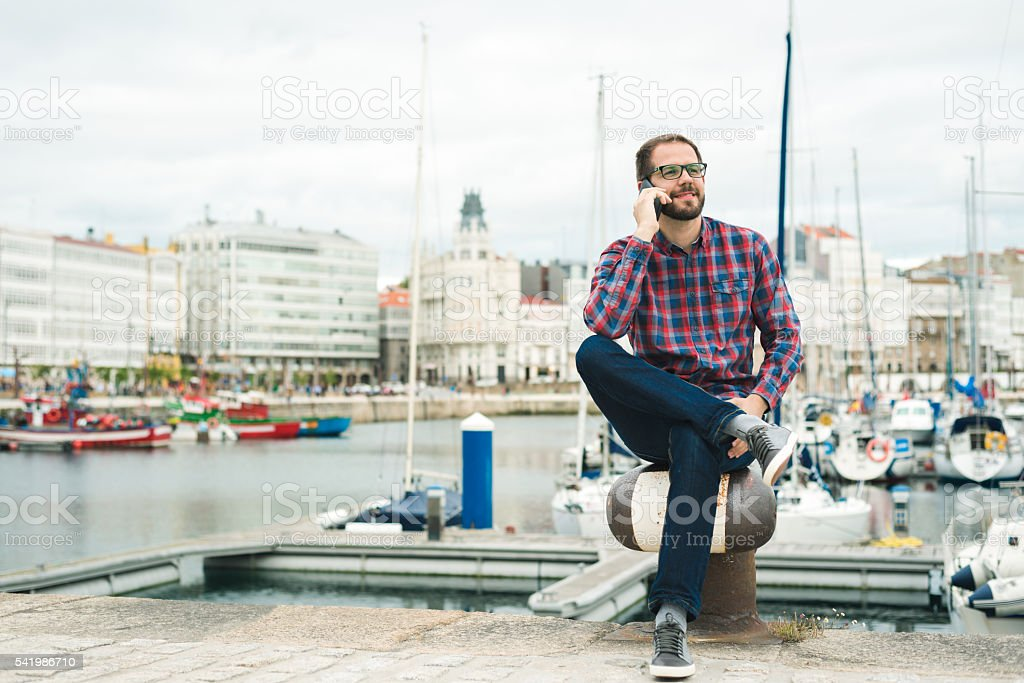bearded man talking on cellphone outdoors at an urban harbour stock photo
