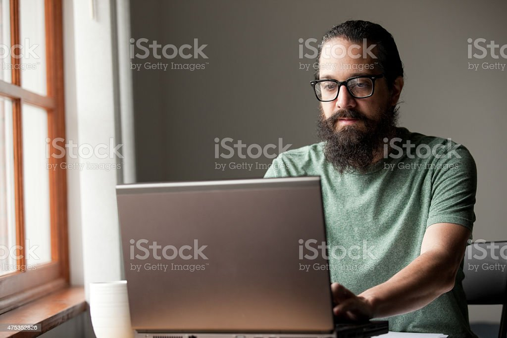 Bearded Man Using Laptop By Window stock photo