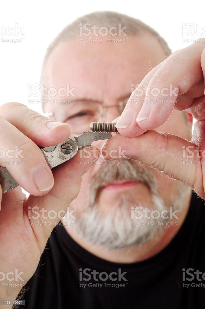 Bearded Man Using Thread-Gauge to Size Screw Thread stock photo