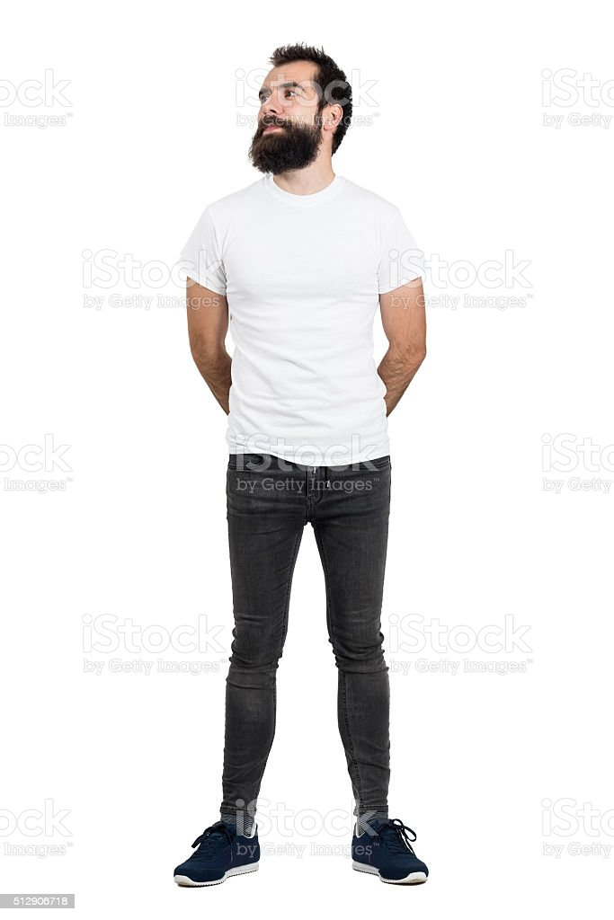 Bearded man wearing white t-shirt and tight jeans looking away stock photo