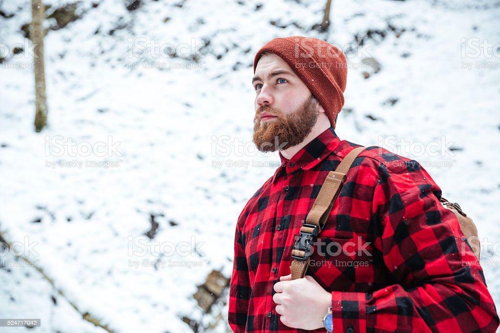 Bearded man with backpack in winter mountain forest stock photo
