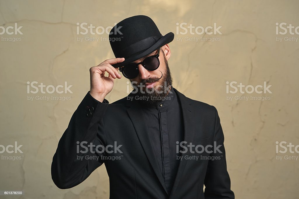 Bearded Man with black Clothes greets stock photo