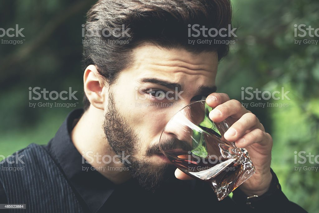 Bearded man with glass of whiskey. stock photo